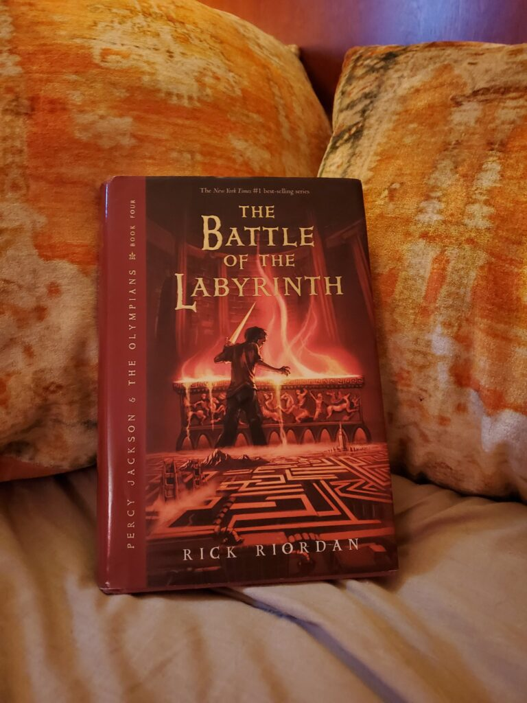 A copy of the book 'The Battle of the Labyrinth' resting on a pile of pillows