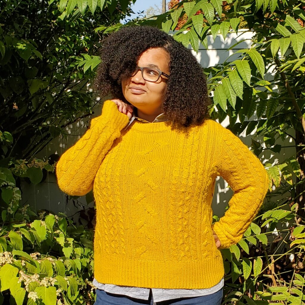 Talia, a person with light brown skin, dark curly hair, and glasses, is smiling in front of a collection of trees and bushes. They are wearing a yellow sweater over a collared shirt and blue jeans.